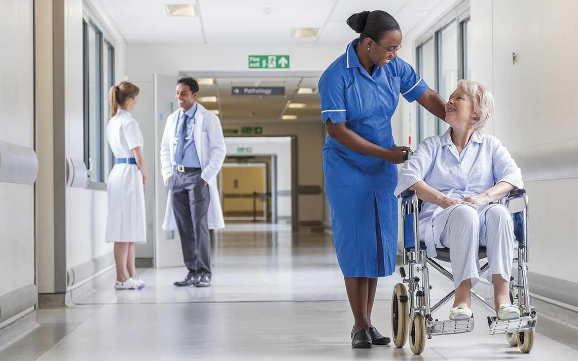 Nurse in corridor with patient in wheelchair