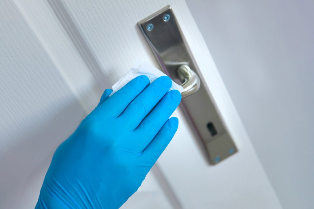 A blue plastic gloved hand cleans a metal door handle